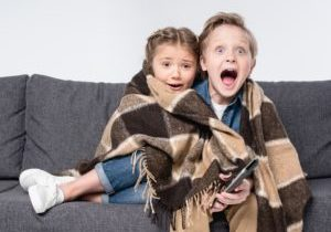 scared brother and sister in blanket watching tv together isolated on white